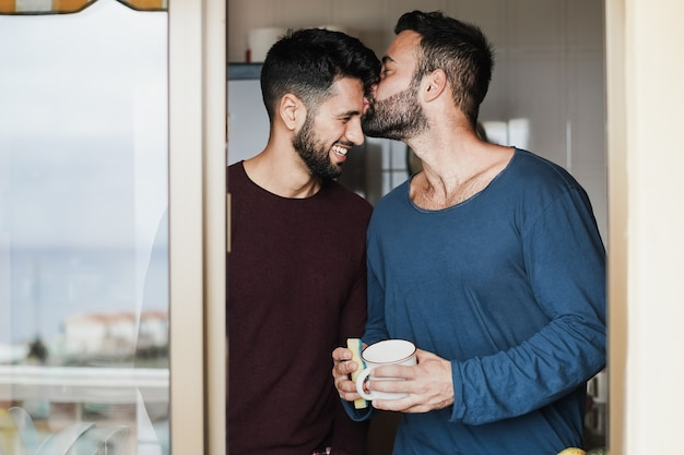 Gay male couple having tender moment while washing dishes inside home kitchen - focus on faces