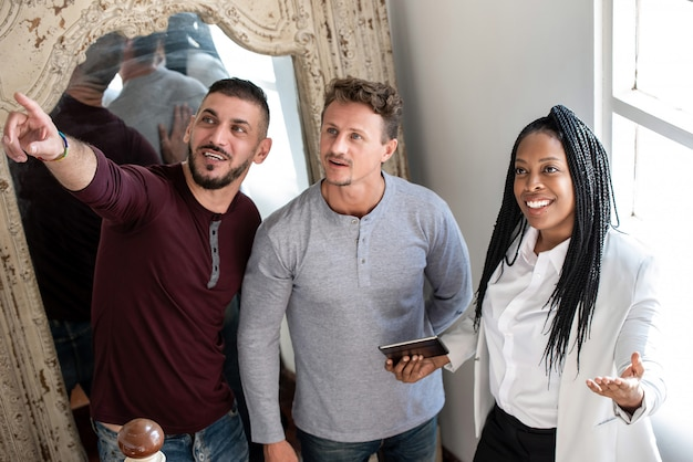 Gay male couple purchasing new house with african american female agent