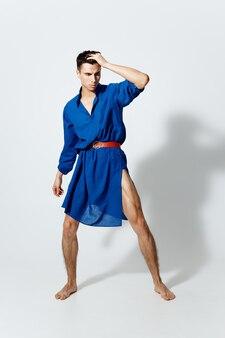 빨간 벨트와 파란 드레스에 게이 남자는 밝은 배경에 그의 다리를 확산