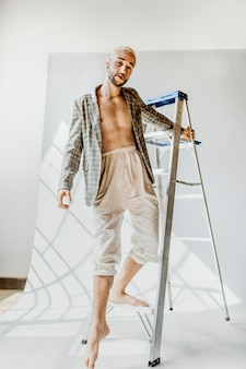 Gay man in a plaid coat posing on a step ladder