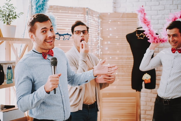 Gay men in colorful clothes singing karaoke at party.
