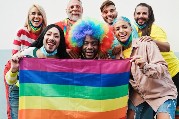 Gay people dance at pride parade with lgbt flags while wearing protective face mask