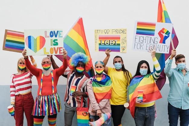 Lgbtの旗やバナーを屋外でプライドパレードで楽しんでいるゲイの人々-主な焦点は年配の男性の顔