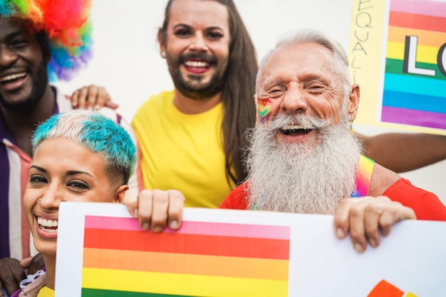 Gay people having fun at pride parade with lgbt banner outdoors - main focus on senior man face