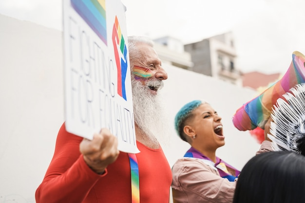 Gay people protest at lgbt pride event outdoor - focus on hipster senior man face