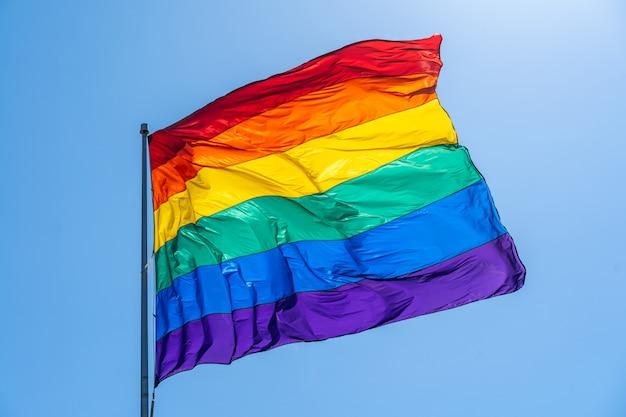 Gay pride flag on a blue sky