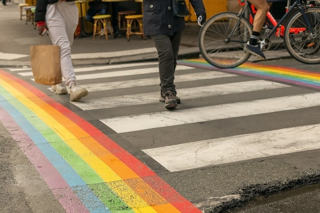 Gay pride flag, rainbow flag of the lgbt community on crosswalk with people crossing in paris. lgbt flag as a symbol of love, freedom, equality, rights concepts in daily life.