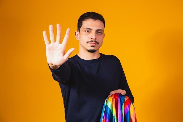게이 프라이드. 그의 손으로 앞으로 편견에 정지 신호를 만드는 동성애 소년