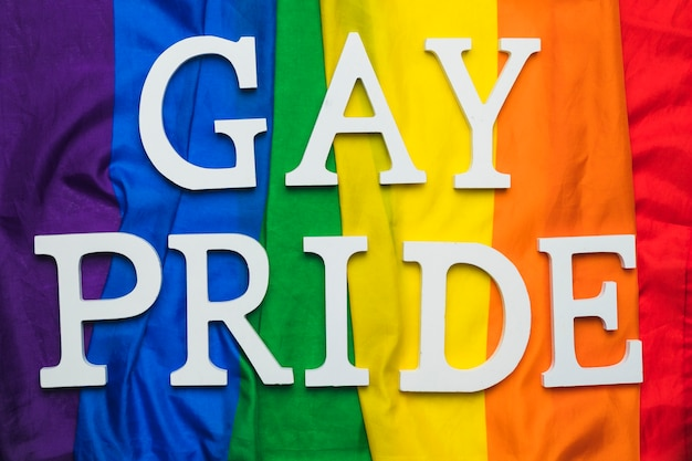 Gay pride lettering on rainbow flag