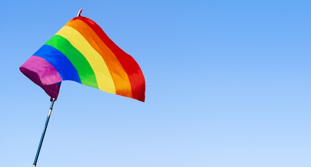 Gay rainbow flag waving in the wind in a clear blue sky