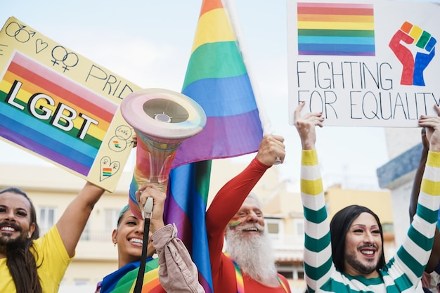 Gay and transgender people protest at pride event outdoor- lgbt and equality rights concept - focus on hand holding megaphone