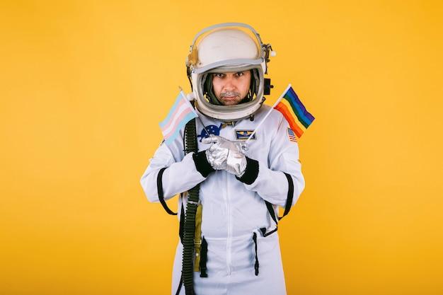 Гей-транссексуал-космонавт-мужчина с серьезным жестом в скафандре и шлеме, держа в руках радужный флаг лгтби и флаг трансгендеров, на желтой стене.