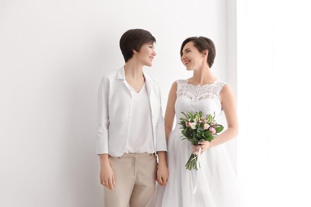 Гей свадебное понятие. счастливая замужняя лесбийская пара на светлом пространстве