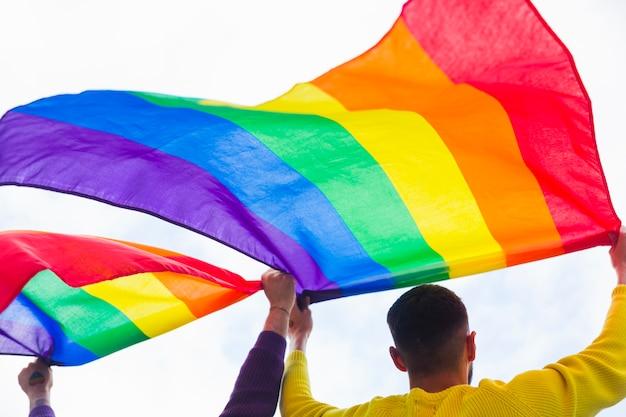 同性愛者のパレードで虹色の旗を保持