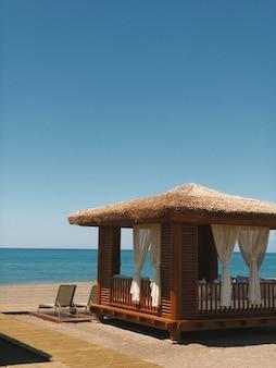 청록색 바다 일광욕 의자 황금빛 모래 푸른 하늘에 의한 전망대