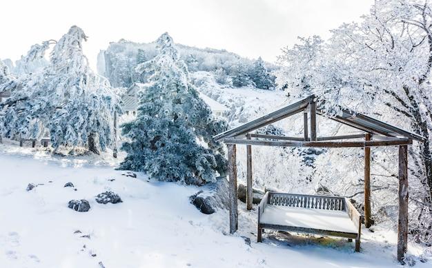Беседка для отдыха в заснеженном лесу в горах.