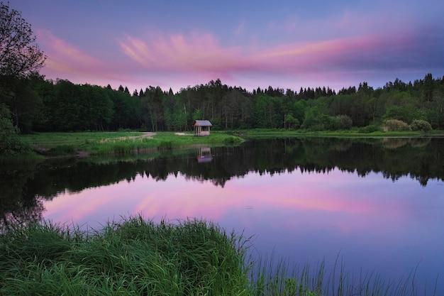 Беседка на берегу лесного озера на закате, летом