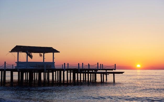 Беседка на деревянной пристани в море с солнцем на закате.