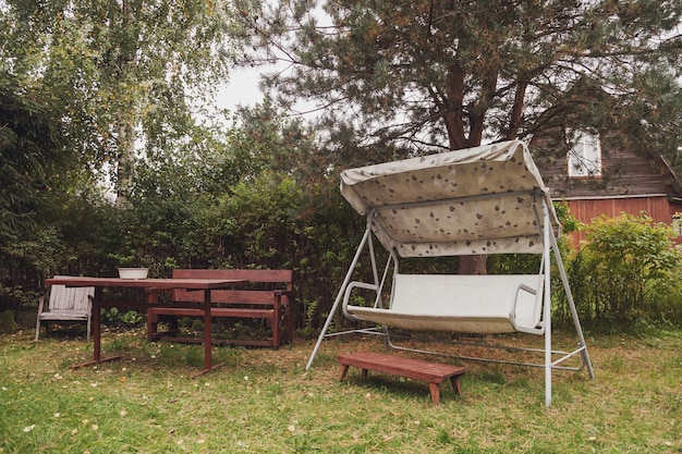 Gazebo, pergola and table in garden at country cottage