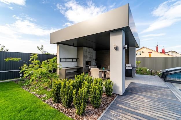 바베큐가 내장된 전망대. 테이블과 의자. 훌륭한 디자인. 주변에 푸른 잔디