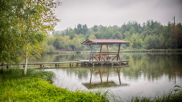 Gazebo with chairs and a table stands on a wooden masonry in the middle of the lake