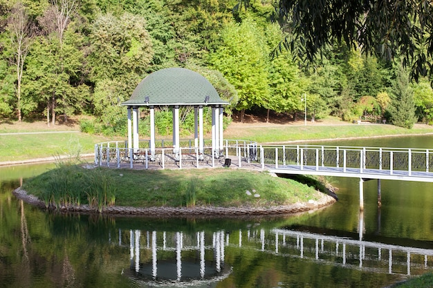 Беседка с кованым мостом, прудом и фоном летнего пейзажа.