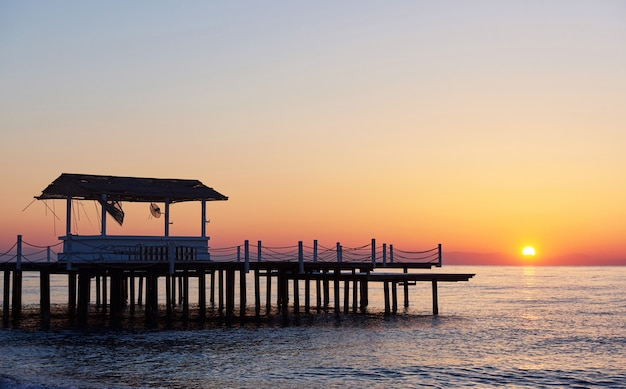 Gazebo on the wooden pier into the sea with the sun at sunset.