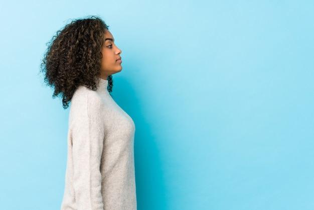 Молодая афро-американская женщина вьющиеся волосы gazing налево, косое представление.