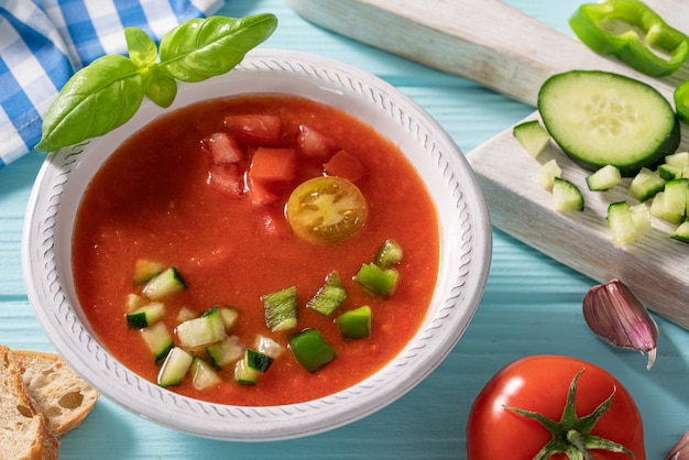 Gazpacho andaluz is an andalusian tomato cold soup from spain with cucumber, garlic, pepper on light blue table