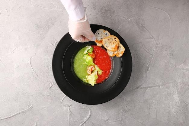 ガスパチョスープの上面図。トマトとキュウリ。緑のスープ。サラダとエビ添え。