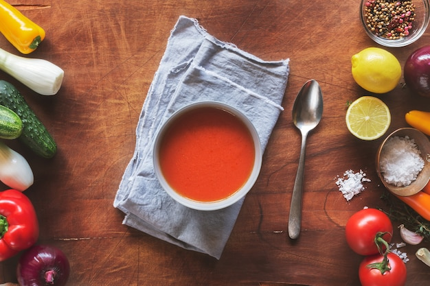 Gazpacho soup with fresh vegetables on wooden surface