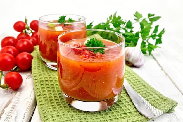 木の板の背景に緑のナプキンにパセリと野菜と2つのグラスのガスパチョトマトスープ