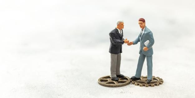 ビジネスにおけるギアのコンセプト。スーツを着たビジネスマンは握手し、ギアの上に立ちます。新しい従業員を雇い、契約します。