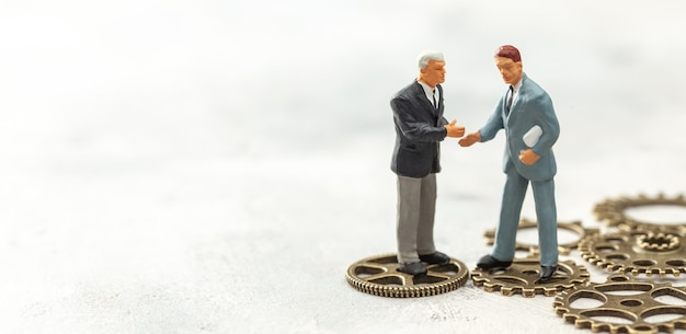 ビジネスにおけるギアのコンセプトスーツを着たビジネスマンが握手し、ギアの上に立つ新しい人を雇う
