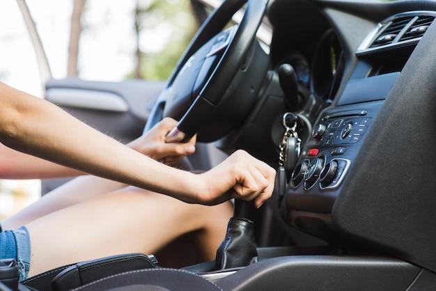 女性ドライバーが付いている車のギアレバー