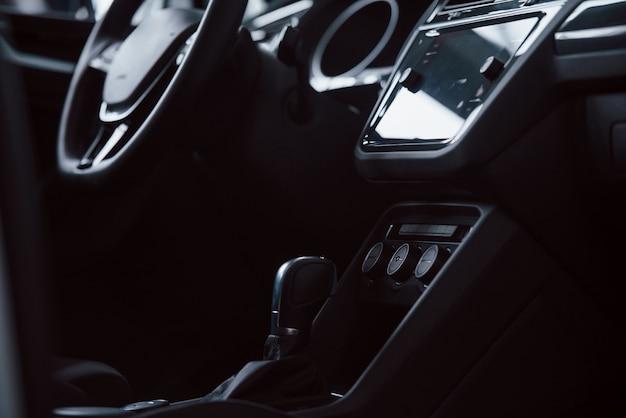 ギアスティック。真新しい自動車の前部。モダンな黒のインテリア。車両の概念