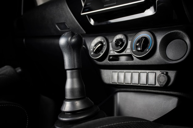 Gear stick of manual transmission of car and air conditioner panel, automotive part concept.