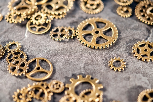 Gears are scattered on a stone background.