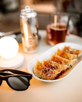 Пельмени гедза на круглом столе кафе с бокалами и пивом