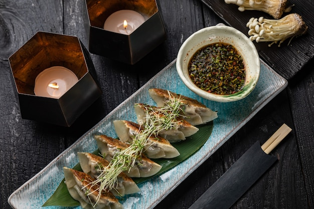 日本食レストランの暗いテーブルにエノキと豆腐を添えたゲッツァ餃子