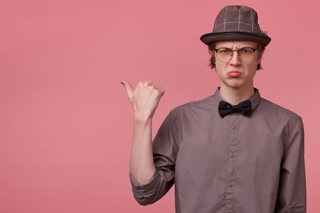 オタクの男は動揺し、彼の唇は否定的な感情に圧倒され、親指を左側に向けるとあなたの注意を引き、ピンクで隔離されたシャツの帽子の蝶ネクタイのメガネでエレガントに服を着せます