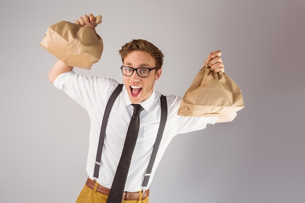 Geeky businessman holding paper bags