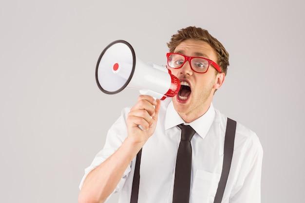 Geeky businessman shouting through megaphone