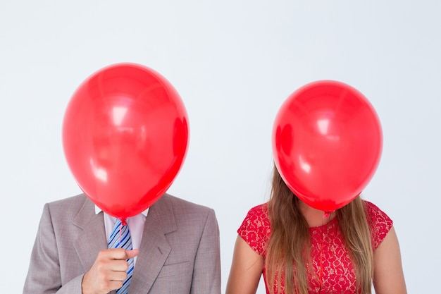 Geeky couple holding balloons in front of their faces