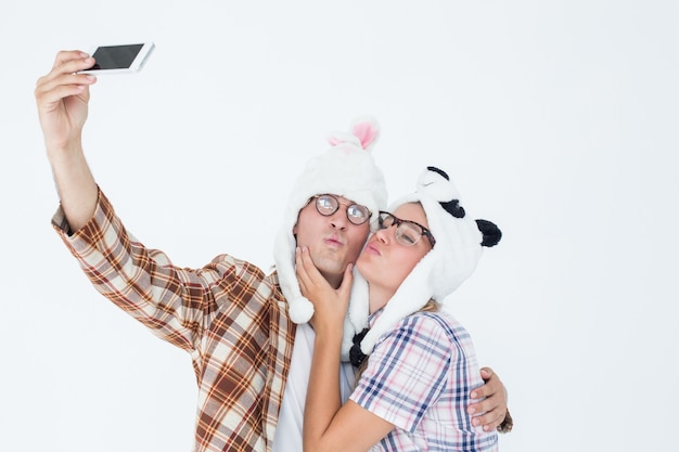 Geeky hipster couple taking selfie with smart phone