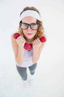 Geeky hipster lifting dumbbells