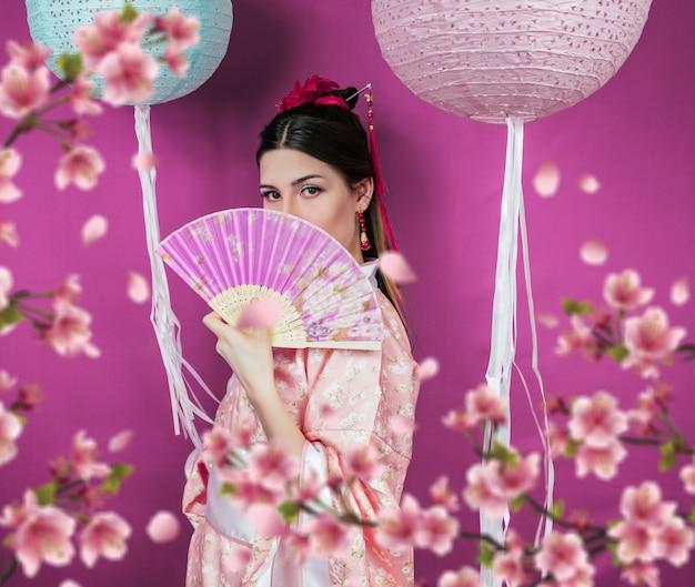ピンクの着物姿の芸者と紫の壁に扇のクローズアップとぼやけた桜の花