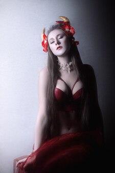 Гейша с рогами и красными цветами на белом фоне в красном бюстгальтере. портрет лица молодой женщины.