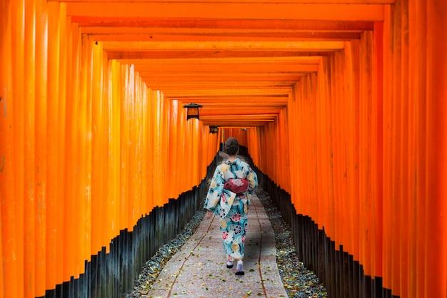 Geishas among red wooden tori gate at fushimi inari shrine in kyoto, japan.