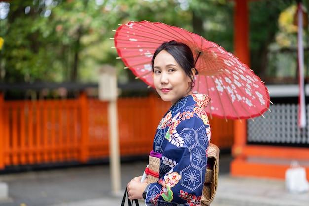 Девушка гейш в японском кимоно среди красных деревянных ворот тори в храме фусими инари в киото,